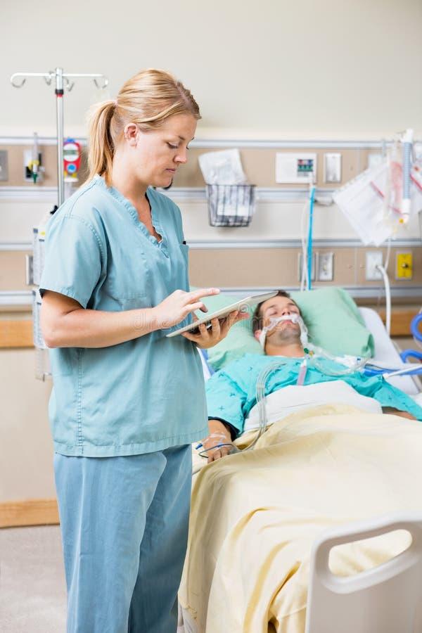 使用数字式片剂的护士,当耐心休息时 免版税库存照片