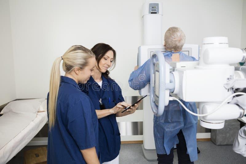 使用数字式片剂的放射学家,当站立的患者在X-射线时 库存照片