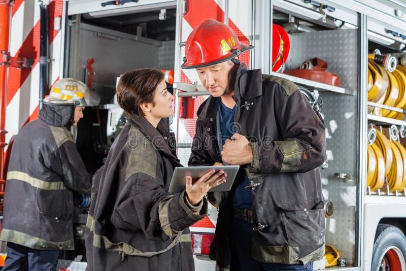 使用数字式片剂的消防队员反对卡车 库存图片