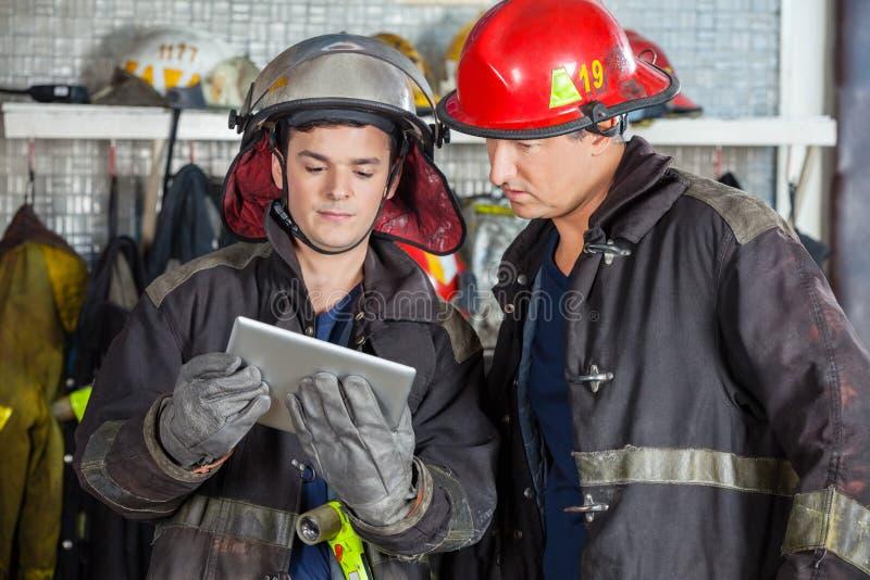 使用数字式片剂的消防队员在消防局 免版税图库摄影