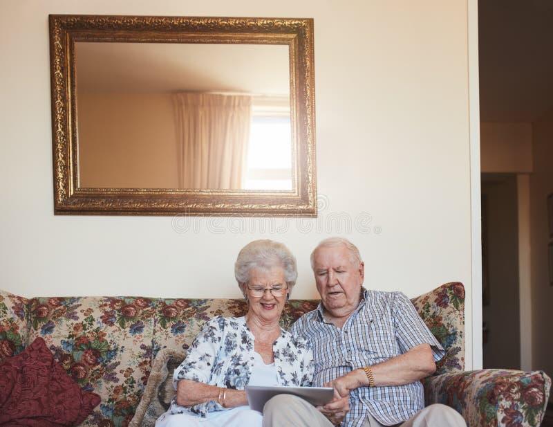 使用数字式片剂的爱恋的资深夫妇在家 图库摄影