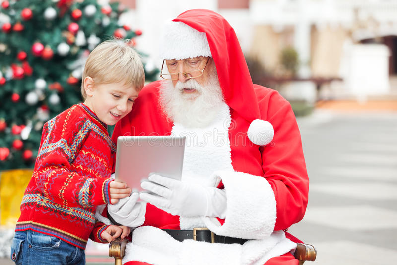 使用数字式片剂的男孩和圣诞老人 免版税库存照片