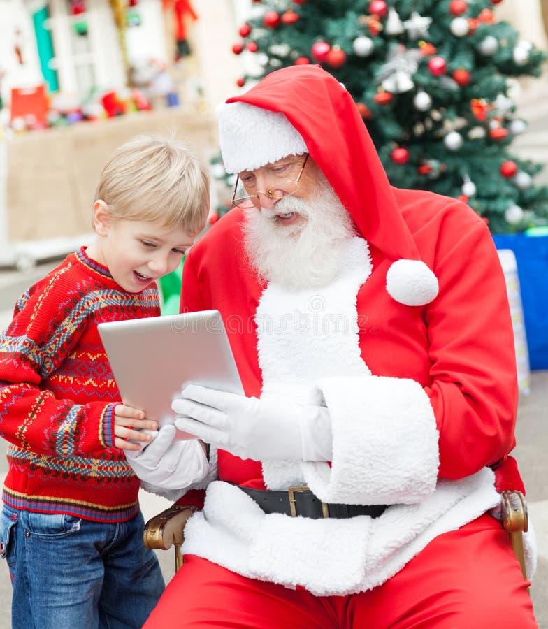 使用数字式片剂的男孩和圣诞老人 库存图片