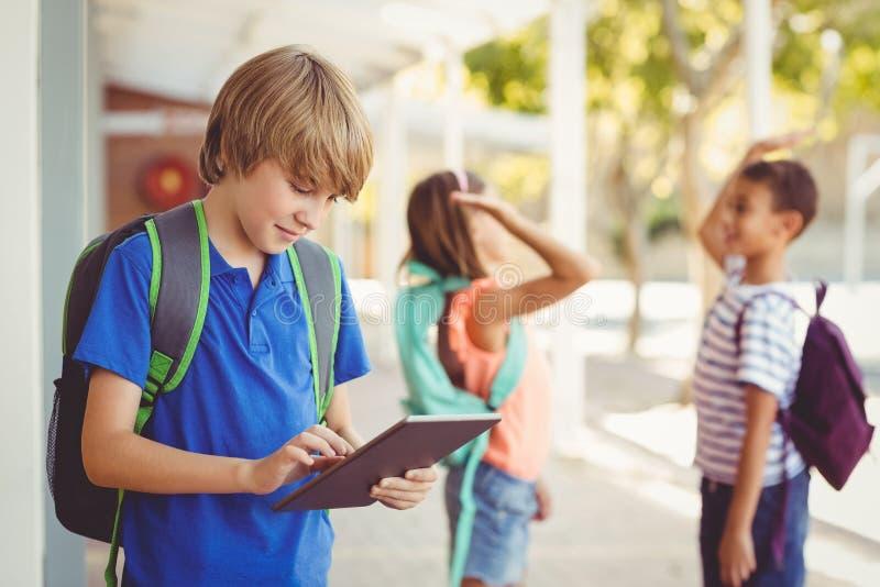 使用数字式片剂的男小学生在学校走廊 图库摄影