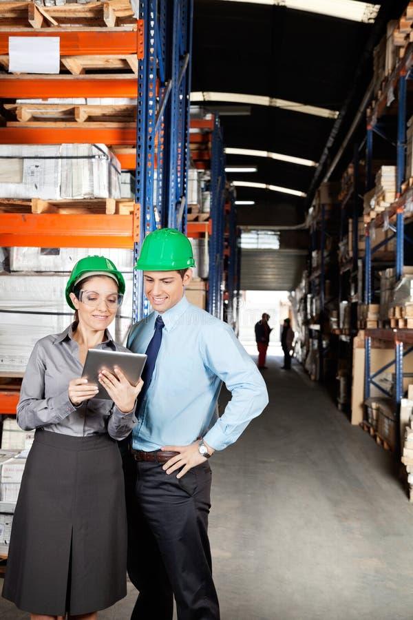 使用数字式片剂的监督员在仓库 免版税库存照片