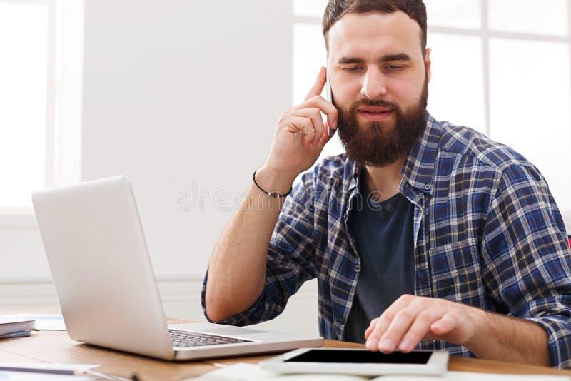 使用数字式片剂的繁忙的年轻商人和谈话在机动性在办公室 免版税库存图片