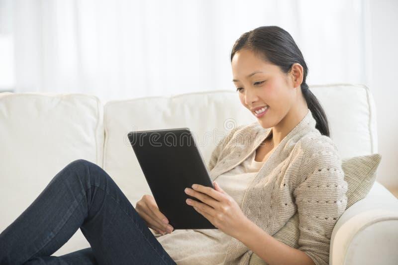 使用数字式片剂的美丽的妇女,当放松在沙发时 免版税图库摄影