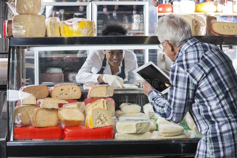 使用数字式片剂的老人在乳酪商店 免版税库存图片