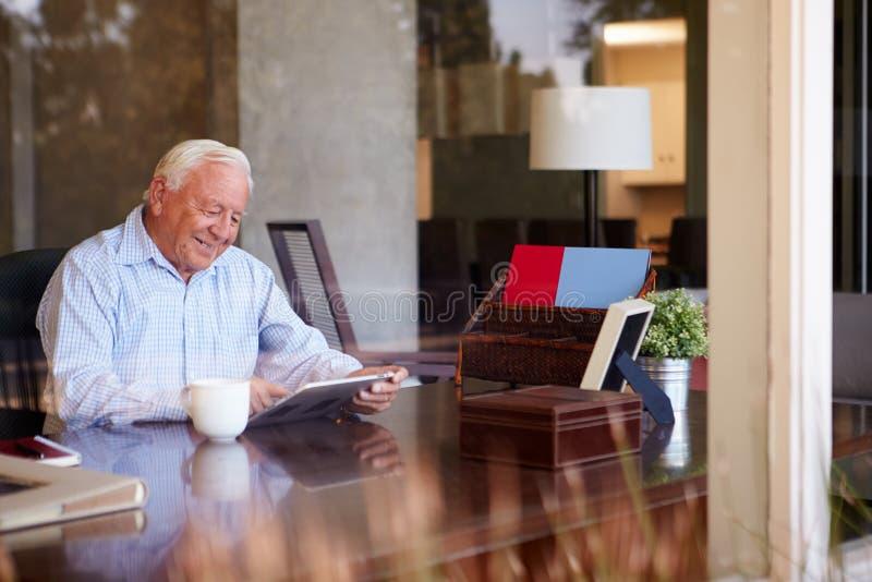 使用数字式片剂的老人通过窗口 库存照片