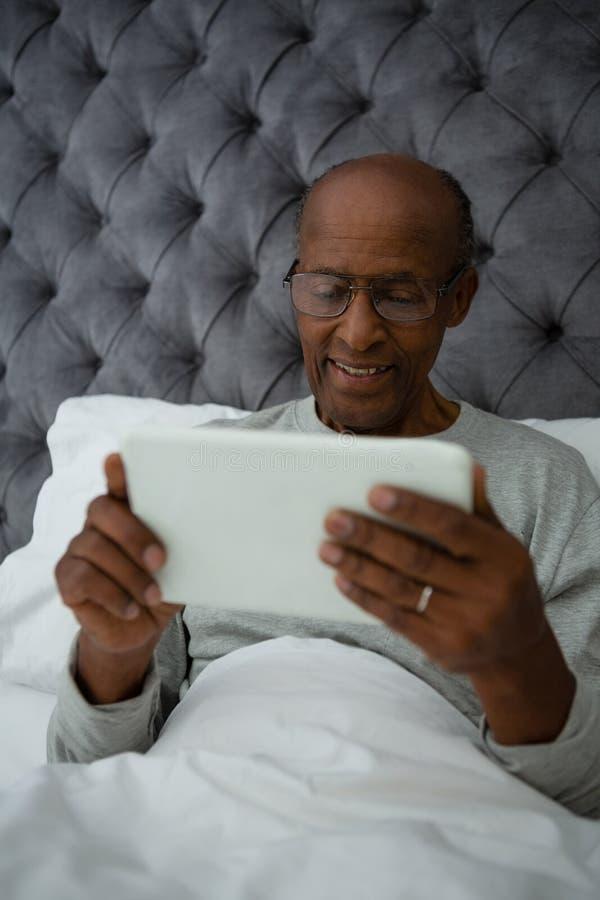 使用数字式片剂的老人,当基于床时 免版税图库摄影