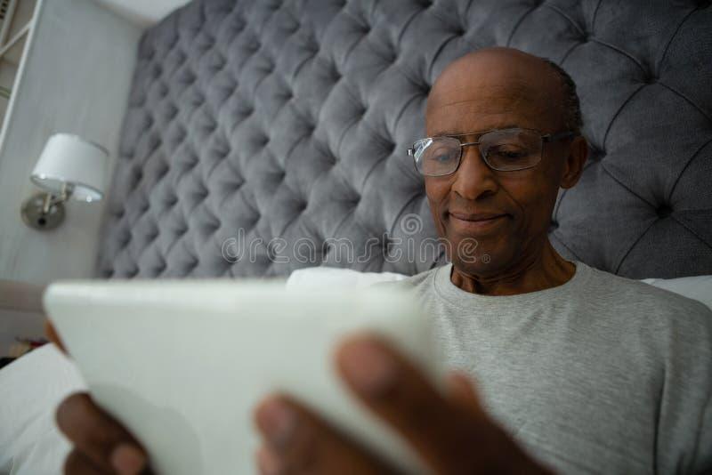 使用数字式片剂的老人,当放松在床上时 图库摄影