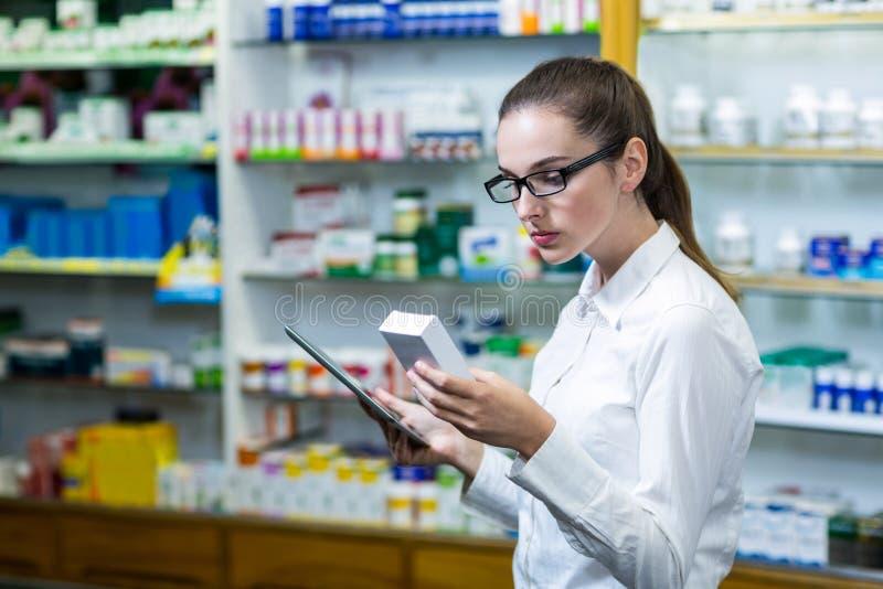使用数字式片剂的药剂师,当检查医学时 免版税库存图片