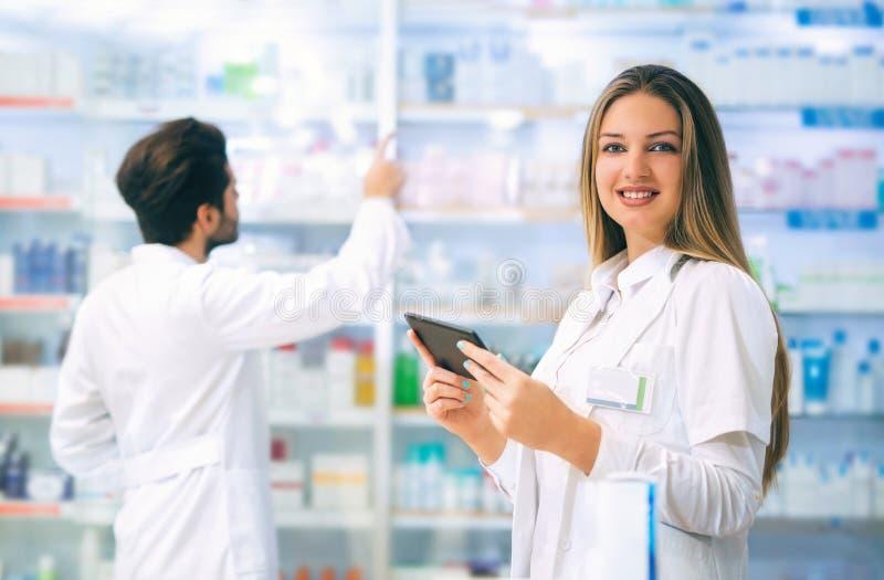 使用数字式片剂的药剂师,当检查医学时 库存图片