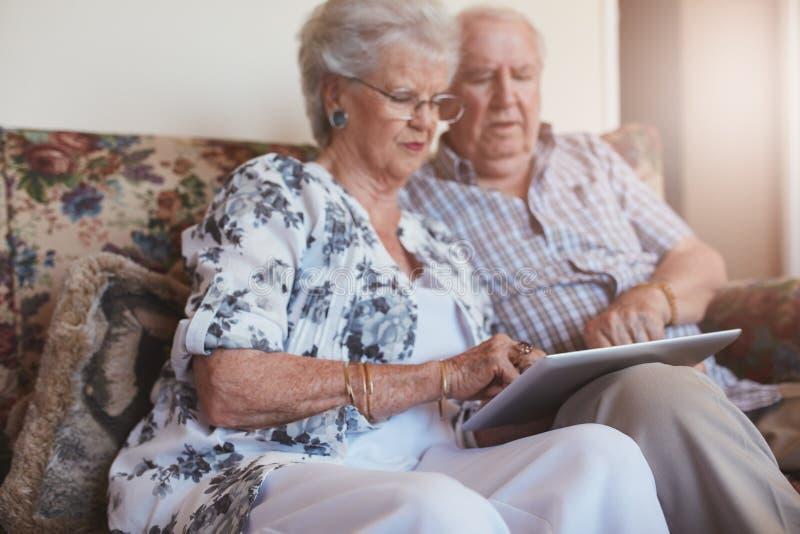 使用数字式片剂的资深夫妇在家 免版税库存照片