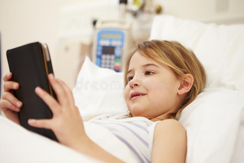 使用数字式片剂的年轻女性患者在医院病床 免版税库存照片