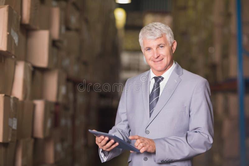 使用数字式片剂的经理在仓库 免版税图库摄影