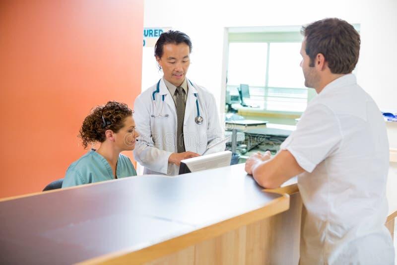 使用数字式片剂的医疗队,当患者时 免版税库存照片
