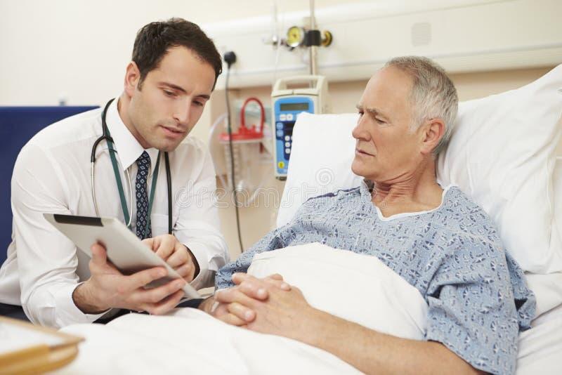 使用数字式片剂的Sitting By Male Patient医生的床 库存图片