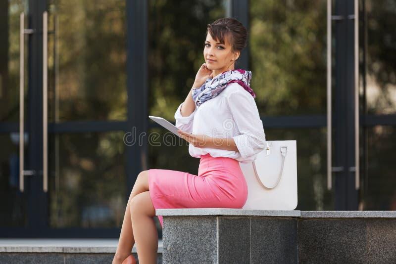使用数字式片剂计算机的年轻时装业妇女在办公楼 库存照片