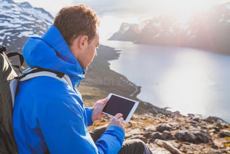 使用数字式片剂计算机的旅客背包徒步旅行者外面在山 图库摄影