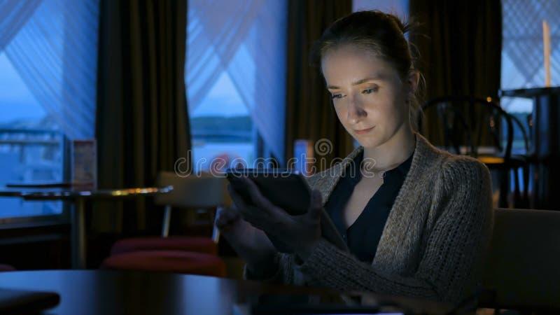 使用数字式片剂计算机设备的妇女在咖啡馆 库存照片
