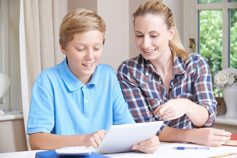 使用数字式片剂,女性家庭家庭教师帮助有研究的男孩 库存照片