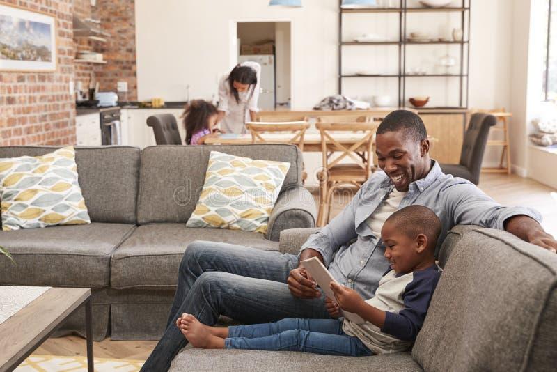 使用数字式片剂,父亲和儿子坐沙发在休息室 库存照片