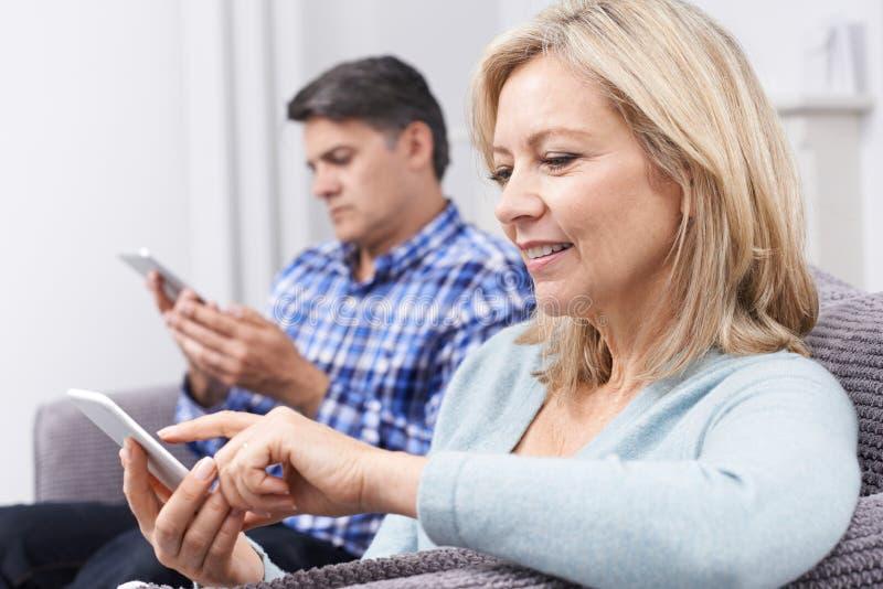 使用数字式设备的成熟夫妇在家 免版税库存图片