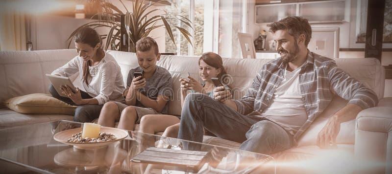 使用数字片剂和手机的家庭在客厅 库存图片