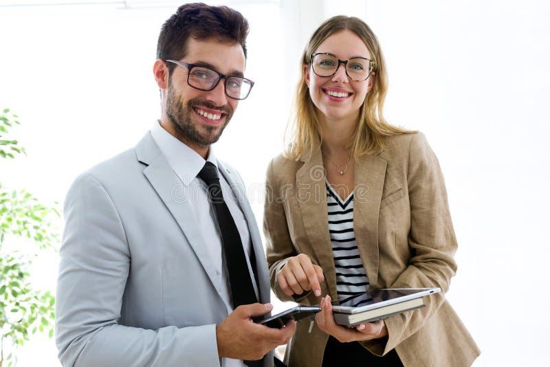 使用数字片剂的两个年轻商务伙伴在走廊他们公司 库存照片