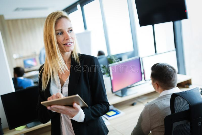 使用数字片剂的可爱的女实业家在办公室 库存图片
