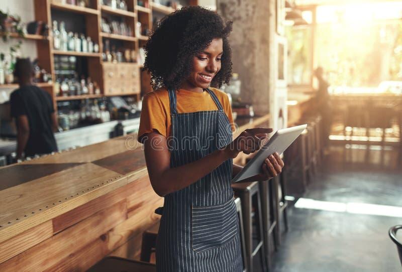 使用数字片剂的女性所有者在咖啡馆 免版税库存图片