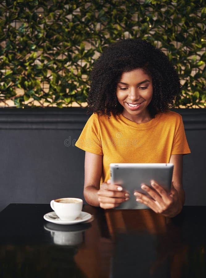 使用数字片剂的年轻女人的画象在咖啡馆 库存照片