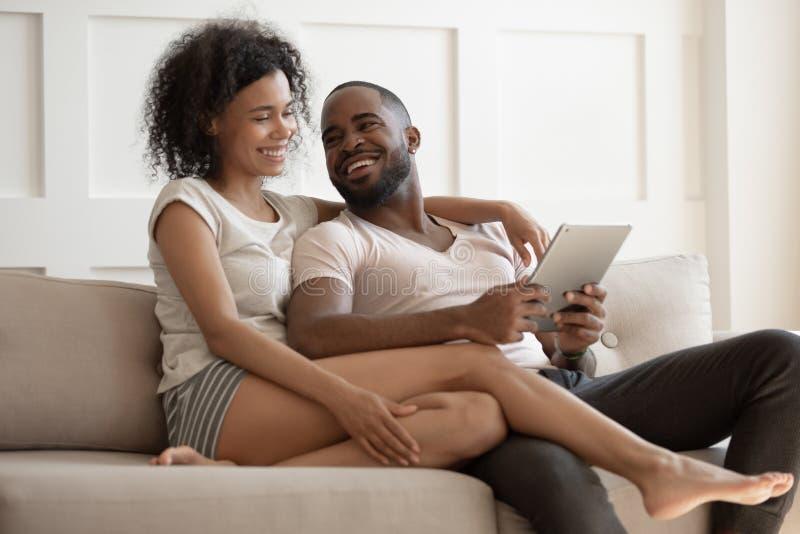 使用数字片剂的愉快的年轻黑夫妇坐沙发 图库摄影