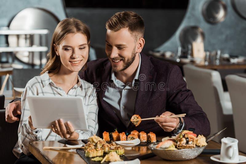 使用数字片剂的有吸引力的夫妇,当吃寿司时 库存照片
