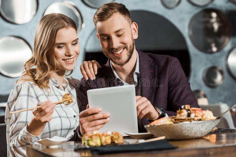 使用数字片剂的有吸引力的微笑的年轻成人夫妇,当吃晚餐时 免版税库存照片