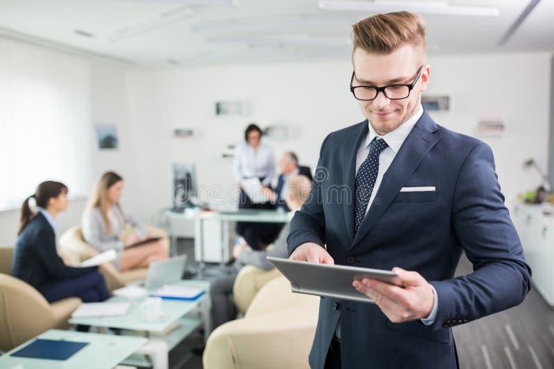 使用数字片剂的确信的商人在办公室 免版税库存照片