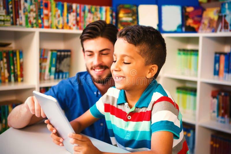使用数字片剂的老师和学生在图书馆 库存照片