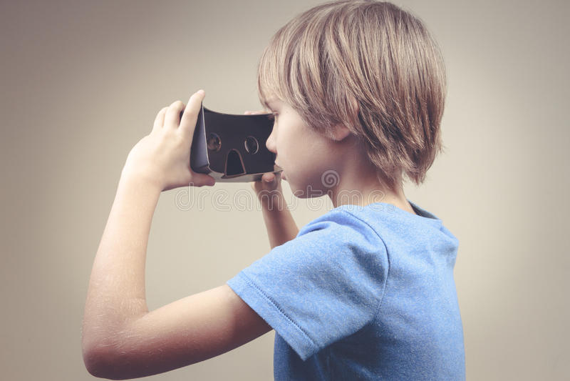 使用新的黑色3D虚拟现实纸板玻璃的孩子 免版税库存图片