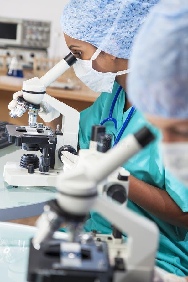 使用显微镜的女性科学研究队在Laborator 免版税库存图片