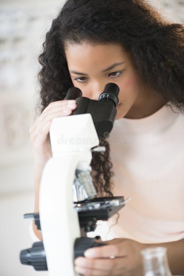 使用显微镜的少年学生 免版税库存图片