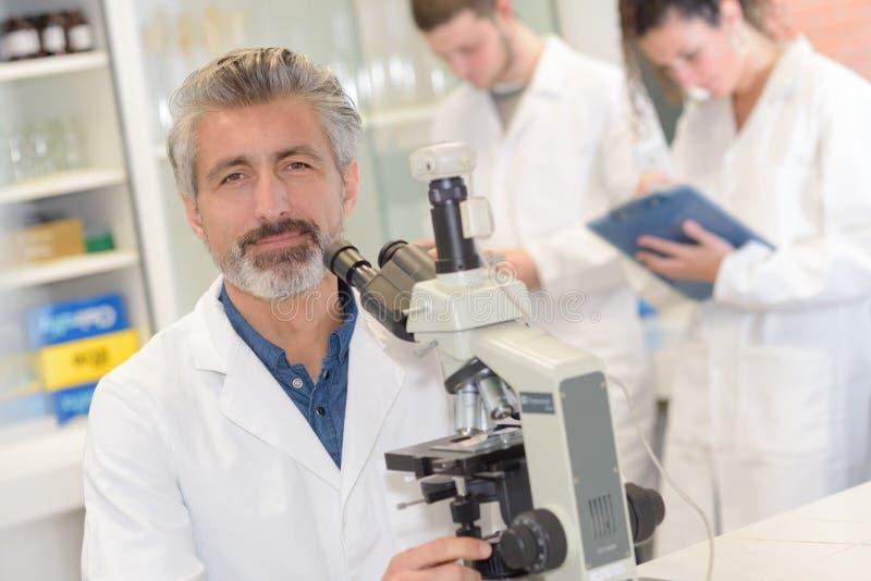 使用显微镜的男性科学研究员在实验室 免版税库存图片