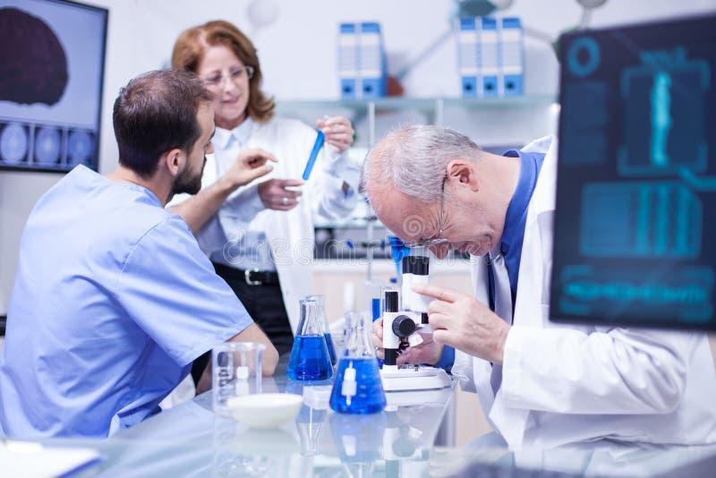 使用显微镜的资深科学家在医院实验室为研究 免版税库存图片