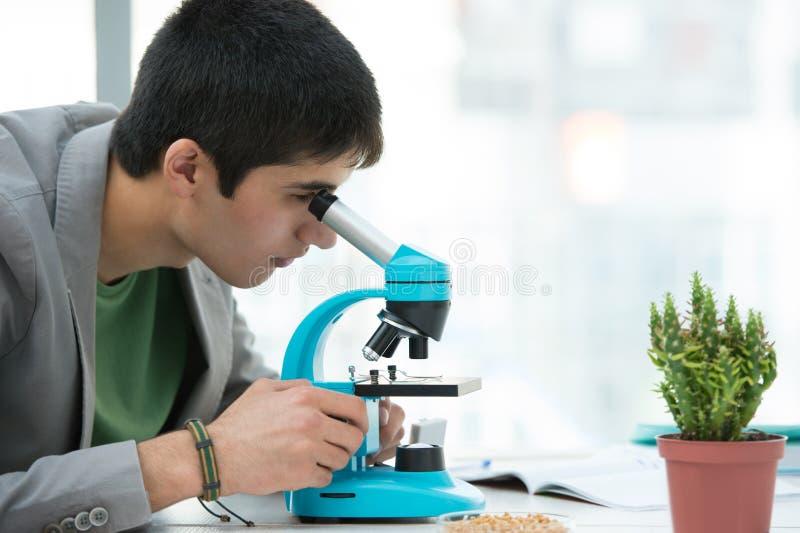 使用显微镜的年轻英俊的男学生 库存照片