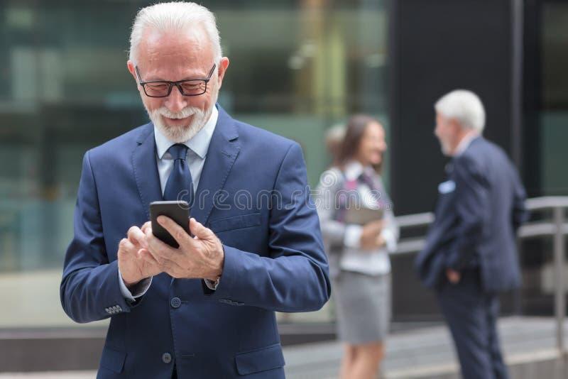 使用智能手机、浏览互联网或者传讯的成功的愉快的资深商人 库存图片