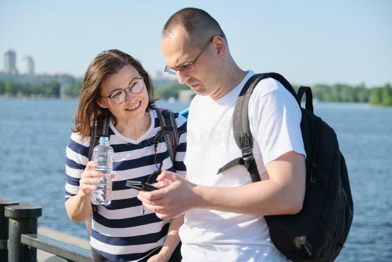 使用智能手机、男人和妇女谈的走的室外成熟夫妇在公园 免版税库存照片