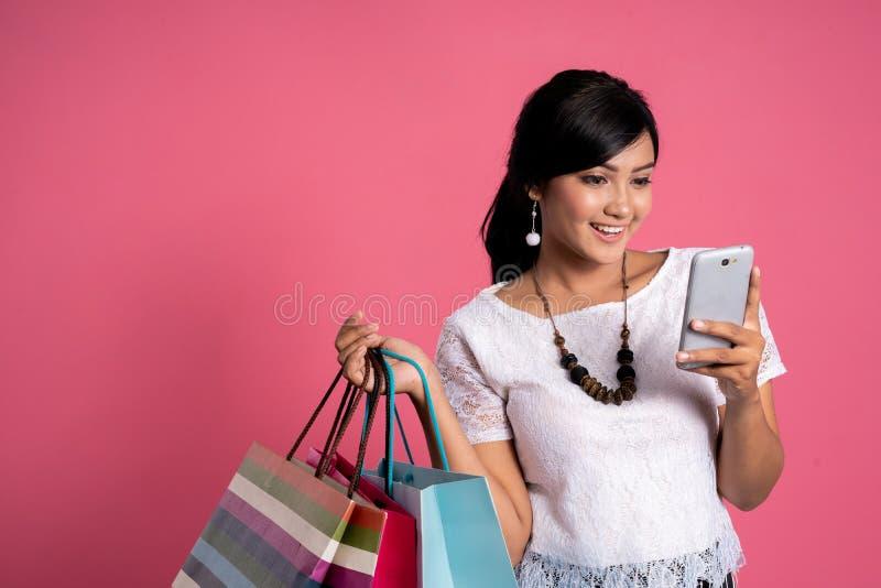 使用智能手机和举行购物带来的购物的妇女 库存照片