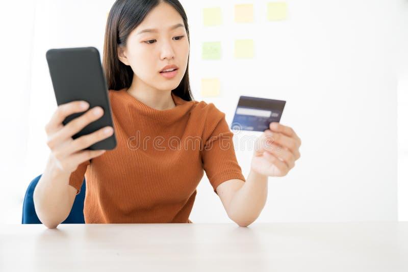 使用智能手机和信用卡的年轻亚裔妇女 在网上购物购买 免版税库存照片