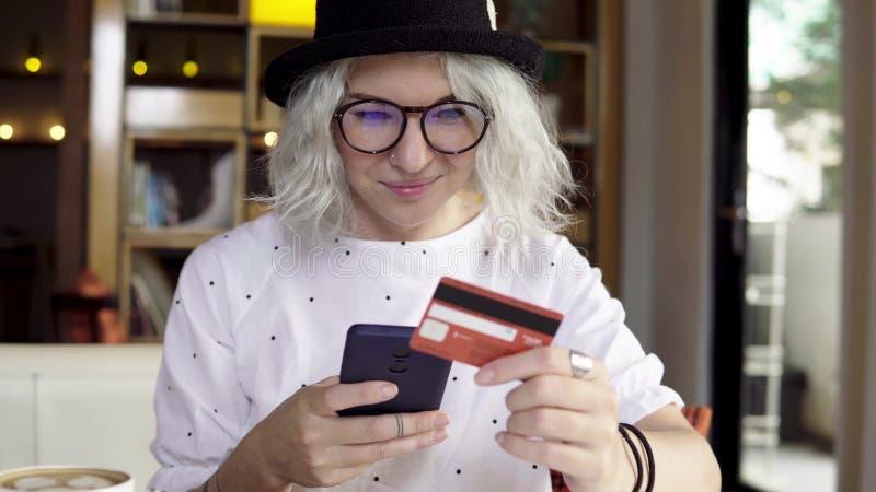 使用智能手机和信用卡,在网上妇女购买新的礼服 免版税库存照片