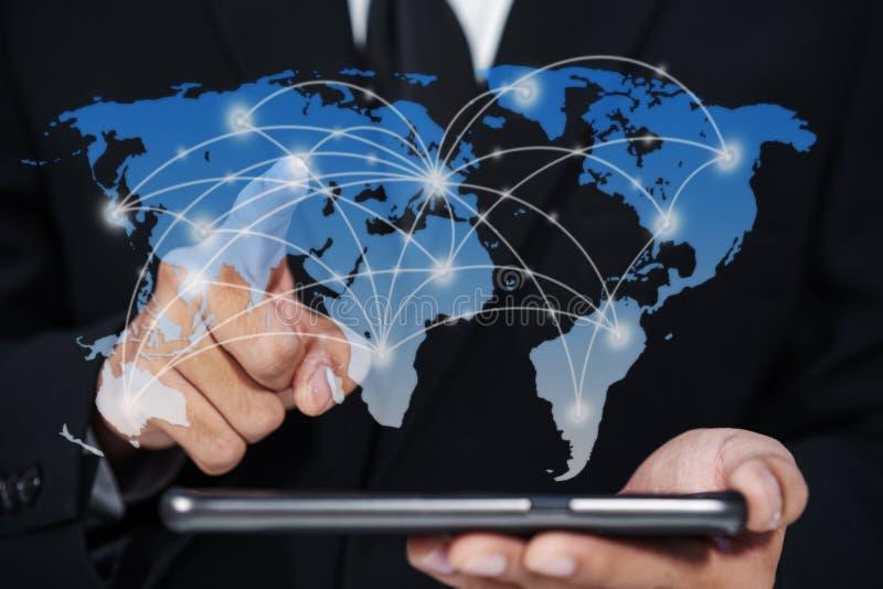 使用智能手机和手的商人接触对世界地图虚象 免版税库存照片